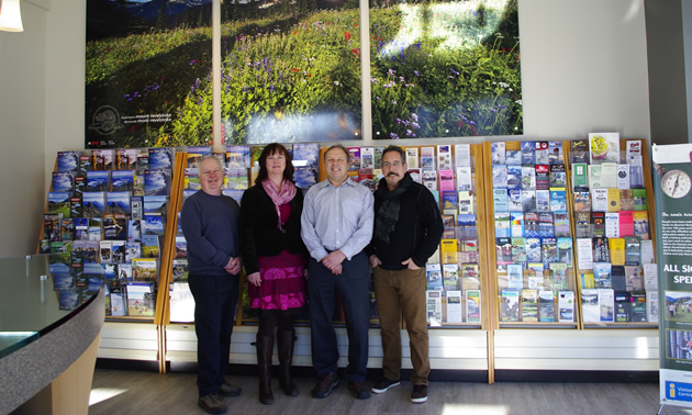 Three men and one woman stand in a row in front of an extensive display of brochures and maps