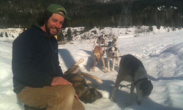 Eric Marsden of Revelstoke Dogsled Adventures kneels next to some of his sled dogs.