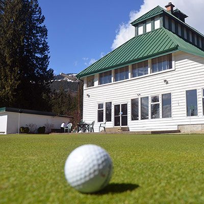 Picture of white golf ball in foreground, with Revelstoke Golf Club in background.