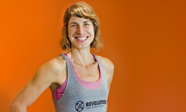 Stephanie China stands against an orange background in her instructor photo for Revelution in Revelstoke, B.C.