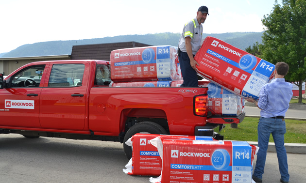 A Rockwool employee stands in the bed of a red Rockwool pickup truck, handing a bag of insulation to a Boundary region homeowner