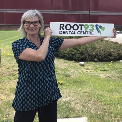 Heather Lang holds a small sign for Root 93 Dental Centre
