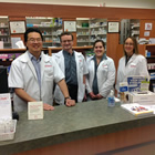 Four white-coated people, two men and two women, stand behind a counter in a pharmacy