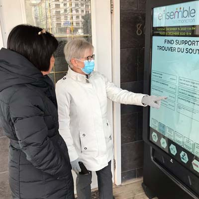 Two people touching a screen on a smart vending machine.