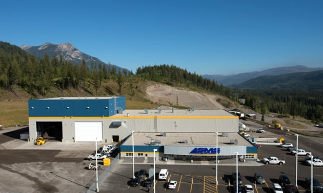 A sprawling building with huge loading doors sits among a beautiful background of mountains and a parking lot.