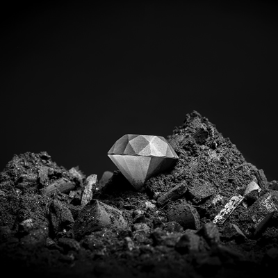 Black-and-white photo of a silvery-coloured diamond on a pile of fine, dark rock rubble
