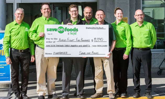 Save-On-Foods managers with large cheque showing total of fundraising efforts.