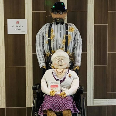 Two scarecrows, an old man standing and an old woman sitting. Staff at Lilac Terrace created the town's winning scarecrows, which were displayed at the mall and voted on by viewers.