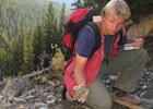 Man looking at rocks in mountains