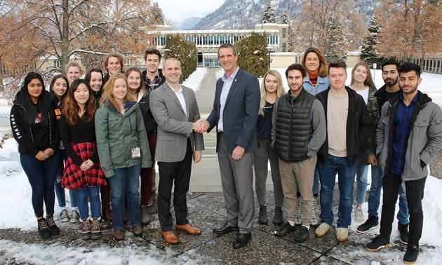 Columbia Basin Trust President and CEO Johnny Strilaeff (middle left) and Selkirk College President and CEO Angus Graeme (middle right) gather in front of Selkirk College's Castlegar Campus with students from a variety of programs to recognize the new partnership that will innovate and enhance the college experience.