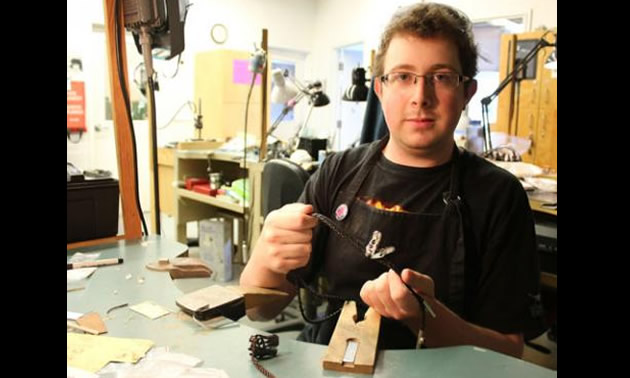 Selkirk College Kootenay Studio Arts student Wade Moravec shows one of his dinosaur-inspired jewelry pieces that will be featured at the annual Year End Show & Sale.