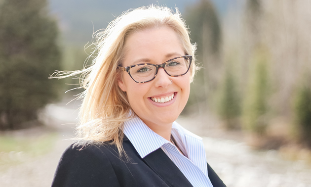 Head shot of smiling young blonde woman wearing glasses and business attire