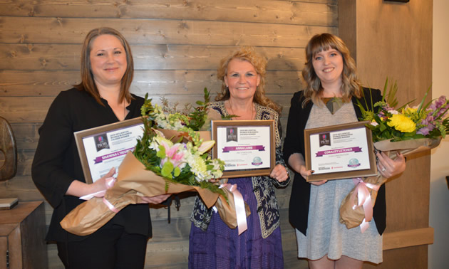 Three smiling  business-women holding bouquets of flowers: Shawna L'Heureux, Zen Mountain Float & Wellness, Kimberley; Anna Lamb, Pro-Fitness Gym,