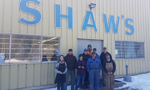 Staff are standing outside their workplace, with Shaw's in big blue letters on the building. Shaw's Enterprises won the Industrial Business Award.