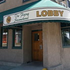 Two-storey, flat-roofed, grey building bears a sign reading Flying Steamshovel Hotel Pub