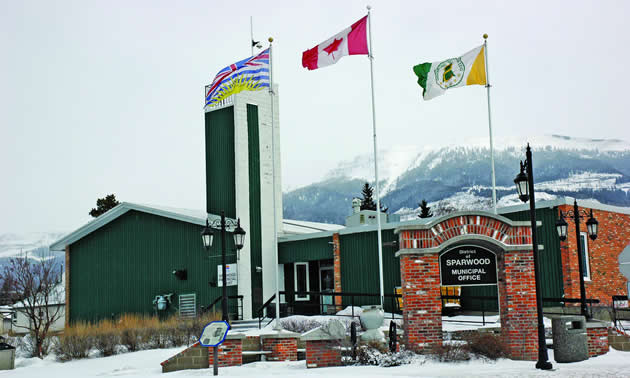Three flags flying outside of a dark green and brick one-storey building, with a sign in the foreground saying District of Sparwood Municipal Office