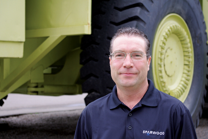 A man stands in front of a giant dump truck