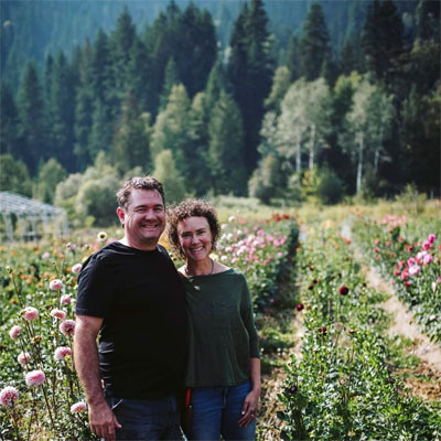 Carl & Sarah Kistner, owners of Stone Meadow Gardens, standing in a field of flowers.