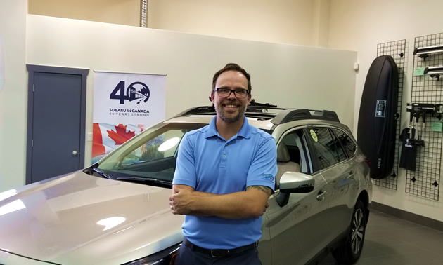 Subaru of Cranbrook's General Manager Jordan McKee stands in front of a new Subaru.
