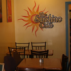 Café seating in front of wall with Sunshine Café beaming sun logo.