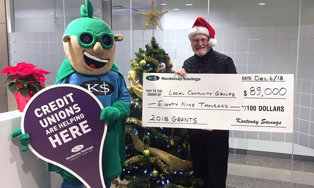 Kootenay Savings Community Foundation Chair Keith Smyth and Kootenay Savings' mascot Super Saver Sam celebrate the good news.