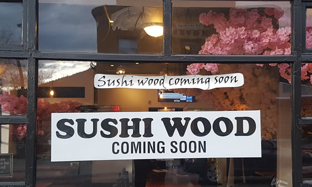 Sign in window advertising the opening of Sushi Wood restaurant.