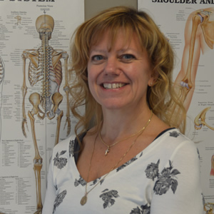 Smiling blonde woman stands in front of anatomical charts