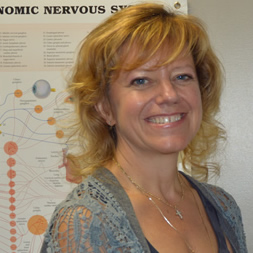 Close-up of a smiling woman with blue eyes and blonde hair, with anatomical charts on the wall behind her