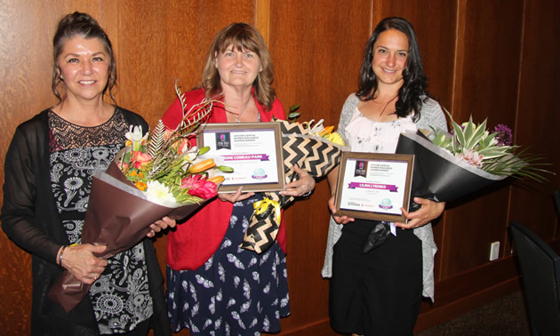 Three smiling business-women holding bouquets of flowers: Tammy Verigin-Burk, Castlegar & District Chamber of Commerce, guest speaker; Simone Comeau-Park, L'Bear's Natural Foods & Supplements, Trail; and Lilina Lysenko, Lysenko Law, Rossland. Not pictured: Judy Banfield, Mountain Baby, Nelson.