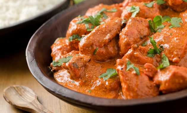 A bowl of spicy red butter chicken is sprinkled with cilantro. Rice, limes and a wooden spoon are in the background.