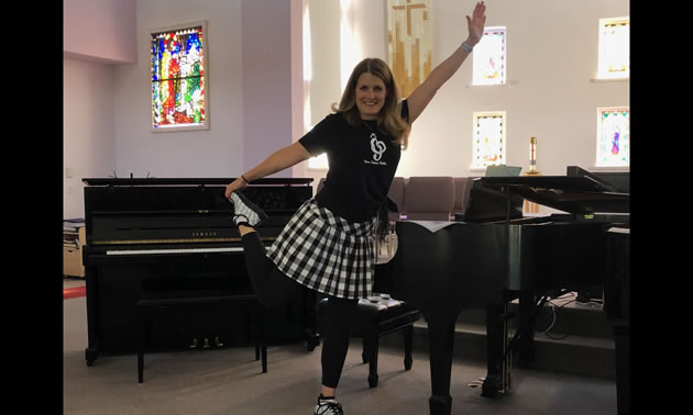 Tanya DuBois is standing in front of a piano, stretching one leg behind her and raising one arm in the air.