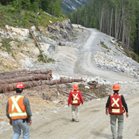 Three workers in safety gear are at their work site on a recently built resource road.