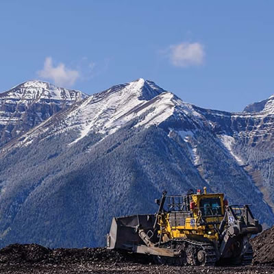 Scenic view of mountains, with worker and construction vehicle in foreground.
