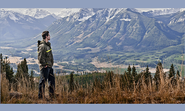 A man stands overlooking a valley with mountains in the background.