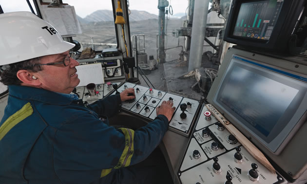 A man wearing a hard hat operating a complex control board with a monitor