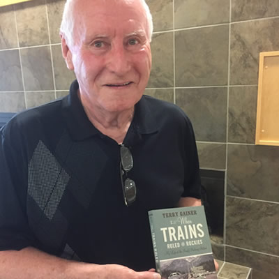 Terry Gainer, holding up his book.