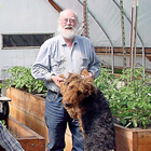 The Haagerup family sits in their greenhouse around plant boxes and smile. Bent is holding the paws of a big dog.