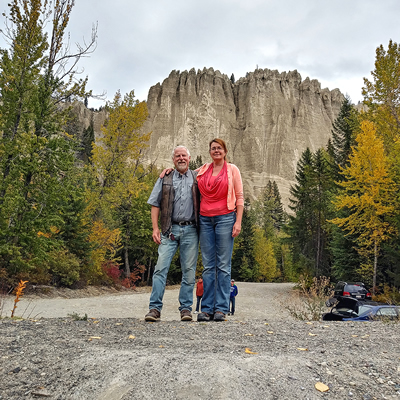 Lorri and Chris McCready, founders of Thör's Pizzeria, stand in front of rock formations in the Kootenays.
