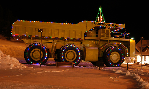 Large yellow haul-truck decorated in Christmas lights and labelled Sparwood, B.C,
