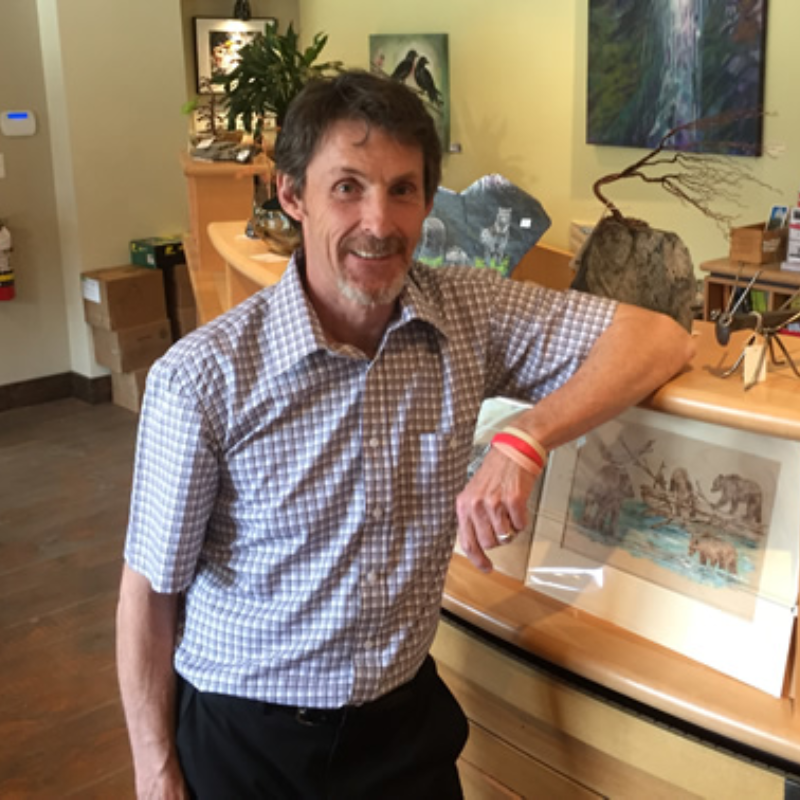 Tom Thomson leans against a desk in the Nelson & District Chamber of Commerce.