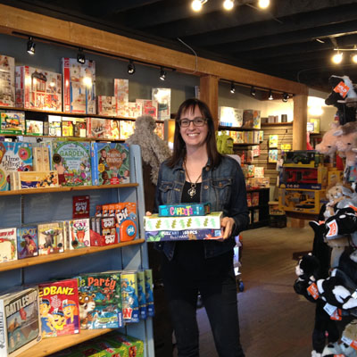 Zoe Ferguson, co-owner of Treehouse Toy Co., holds a stack of games in her newly opened store in Kimberley's Platzl.