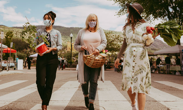 Three women walk through a farmers market.