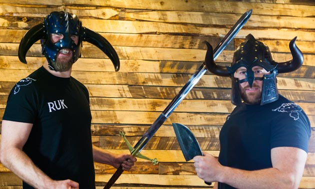 Two people, owners of Ullr's Bar, are wearing Viking hats and holding swords.