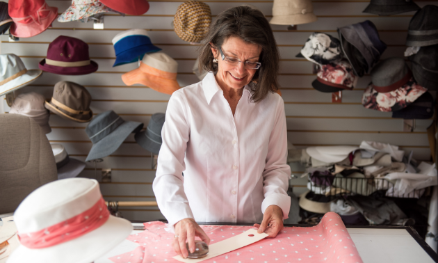 An array of colourful hats surrounding Liz Cohoe demonstrates the variety of headgear that is available from Nelson, B.C.-based company Lillie & Cohoe