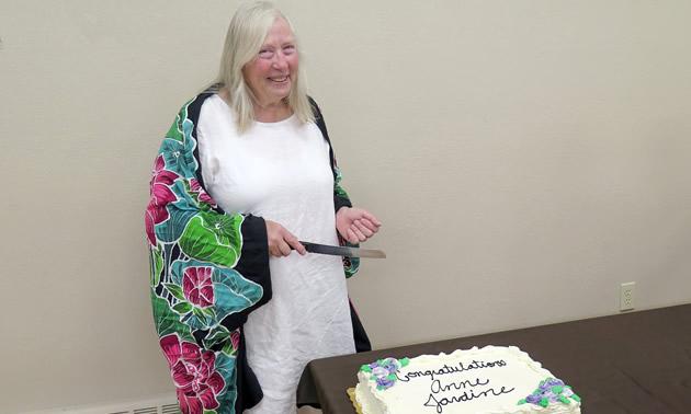 Anne Jardine, preparing to cut cake.