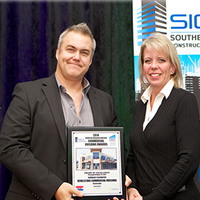 Steve Smith, marketing manager at Vic Van Isle Construction accepts award from Fortis BC representative Shelly Thomson