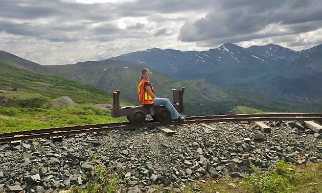 Terwoot sitting on small track equipment on train track, mountains in background.