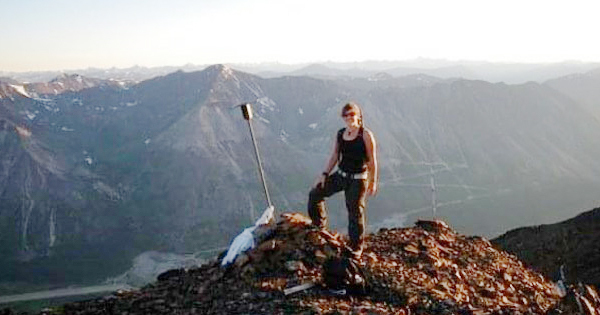Terwoort standing on pile of rocks, mountain vista behind her.