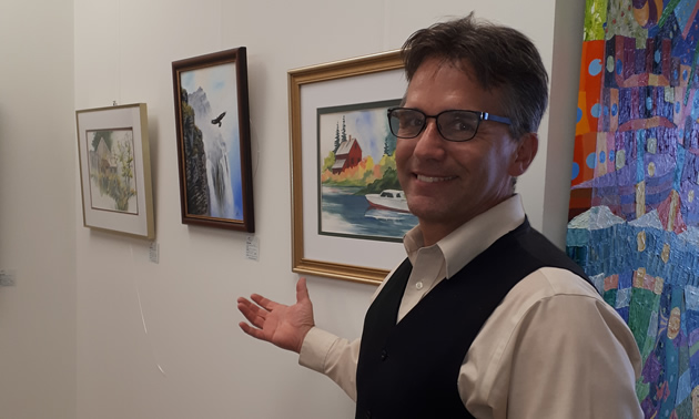 Vern Gorham, manager of the Creston Valley Chamber of Commerce, proudly shows some items of Creston's locally produced art, available in the chamber of commerce building.