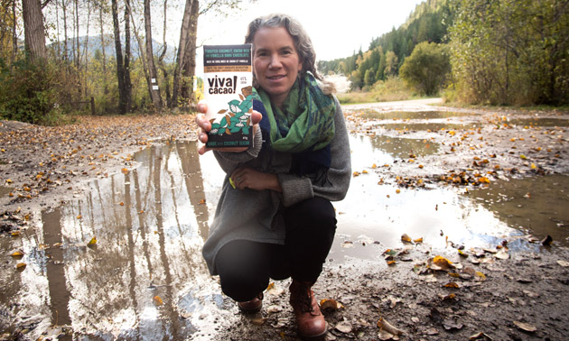 Beth Campbell, owner of Viva Cacao, holding up a bar of her chocolate.